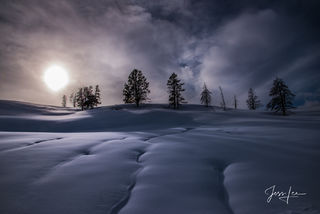 Photograph of the weak winter sun slowy melting the open snow fields of Hayden Valley in Yellowstone National Park.,