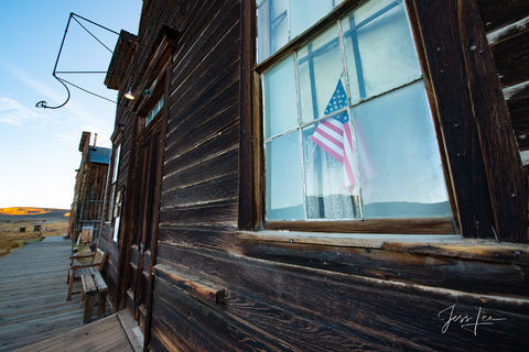 Flag in the window of an old store in Bodie, California