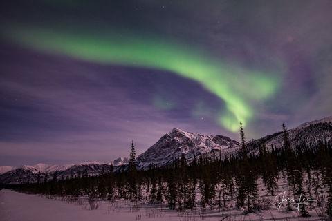 Aurora Borealis over a snow-covered Alaskan mountain range.