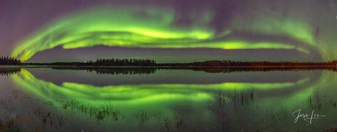 Vibrant green Aurora Borealis reflection in Alaska.