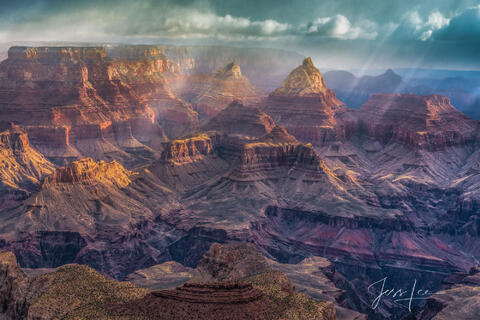 Sun breaking through storm clouds over the Grand Canyon in Red Rocks Country, Arizona.
