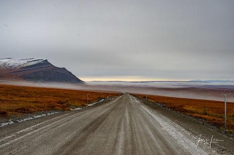 Long stretch of road cutting through Alaska's Arctic tundra.