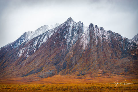 Arctic mountain covered in a thin layer of snow.