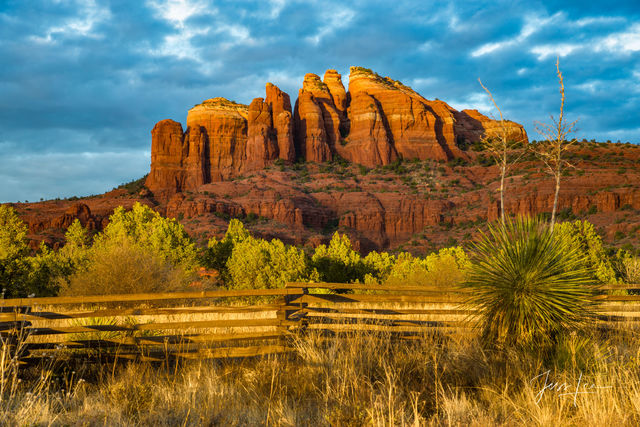 Cathedral Rocks in Arizona, surrounded by native plants and a rail fence.