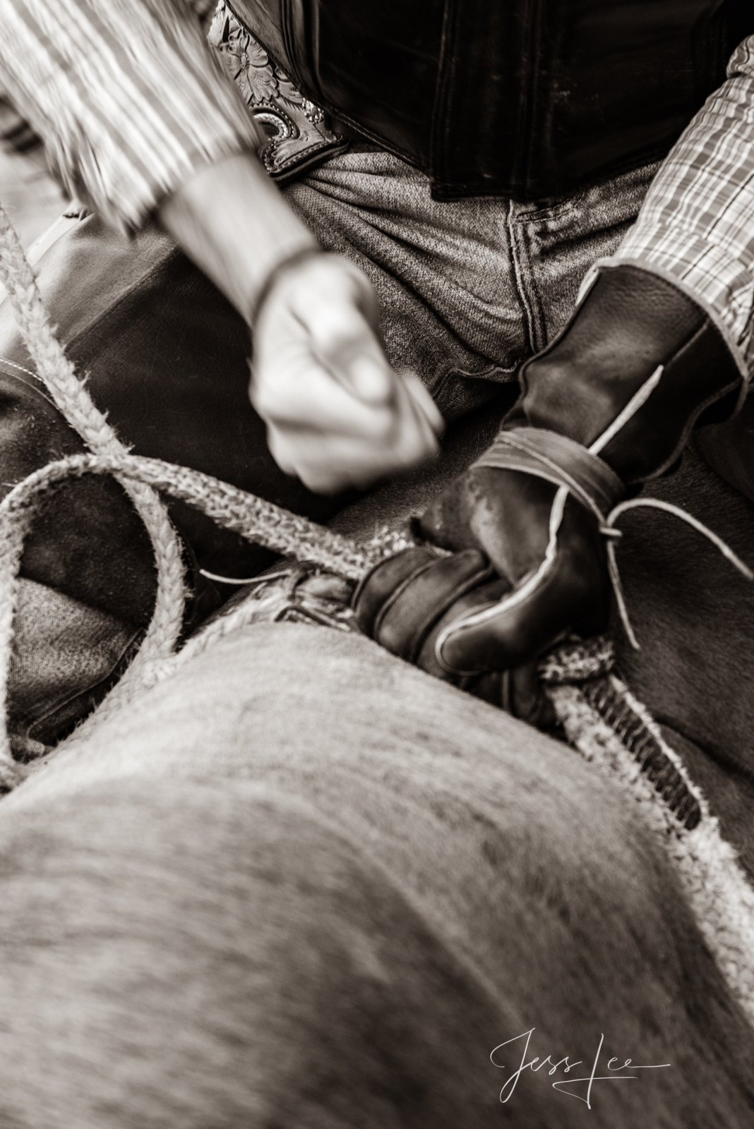 Bull rider hitting his hands to tighten his grip on the rope.