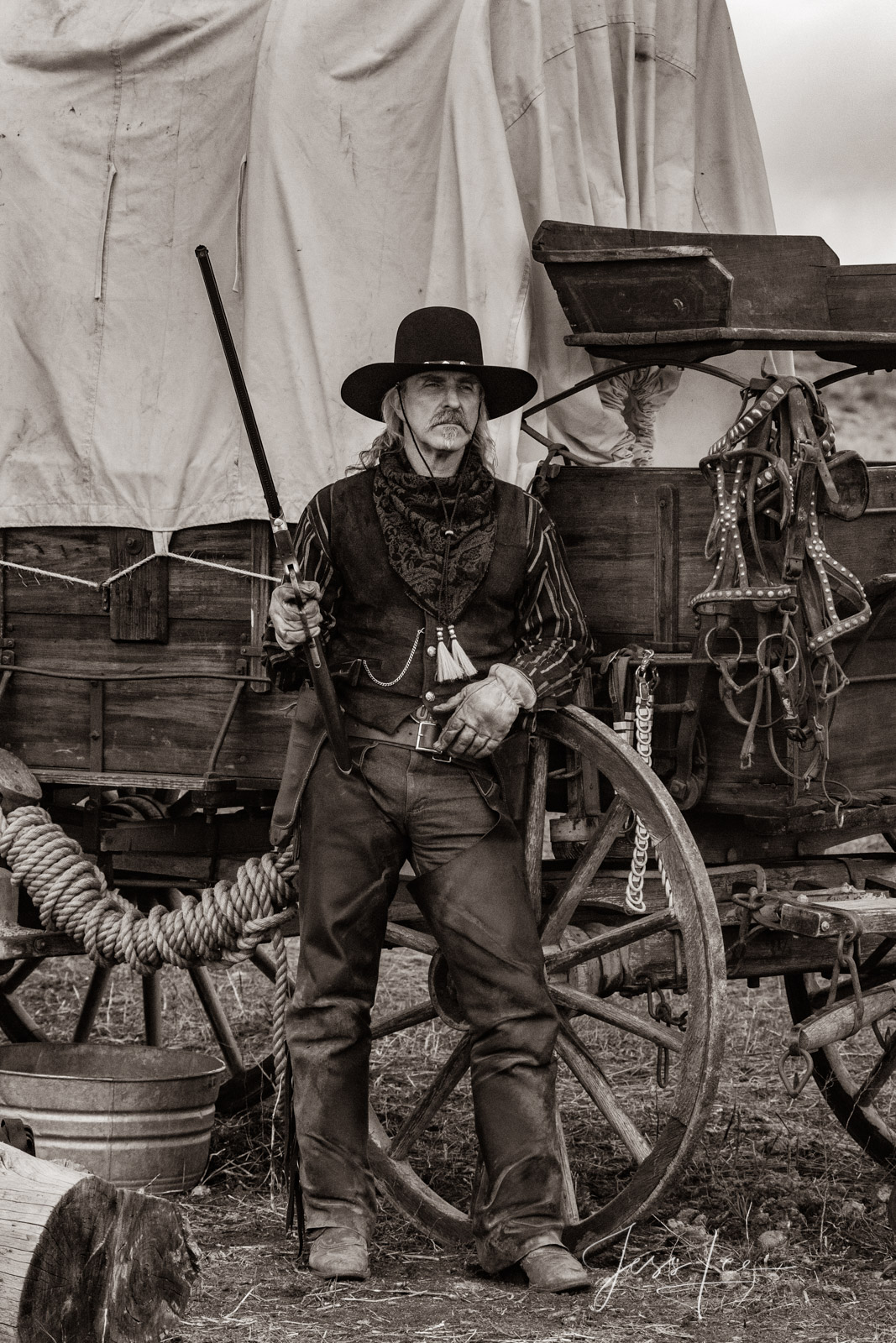 Old Time Cowboy Black and White Sepia Print. Plainsman with Henry Rifle at his covered wagon