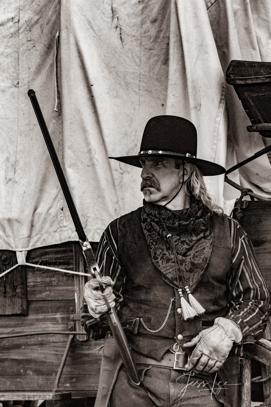 Old Time Cowboy Black and White Sepia Print. Plainsman with Henry Rifle at wagon.